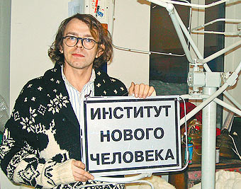 "Sergey Bugaev-Afrika holds a placard for his ""Institute of the New Mankind"""